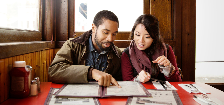 a couple looking through an optimized restaurant menu design